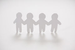 Row of paper cut-out figures. On white background Stock Images