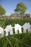 Row of paper houses. A row of 4 paper cut out houses set in the grass, against a background of a townhouse development Stock Images