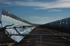 Row of parabolic mirrors. At solar energy plant. Parabolic reflectors are used to collect energy from a distant source (in this case the sun) and bring it to a royalty free stock image