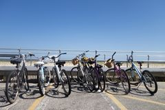 Row or parked bikes at a beach boardwalk sea shoreline. Bicycles on the sreet close to sandy shoreline Royalty Free Stock Images