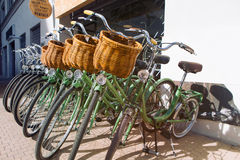 Row of parked vintage bicycles bikes for rent on sidewalk. Green Color. Stock Photo