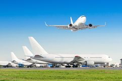 Row of passenger aircraft, airplane parked on service before departure. at the airport, other plane push back tow. One take off fr Stock Photos