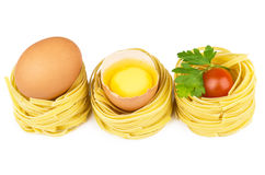 Row of pasta in form nest, egg and yolk Royalty Free Stock Image