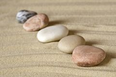 Row of pebbles on sand Stock Image