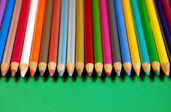 Row of pencil crayons. Row of colored pencil crayons on green background Stock Photography