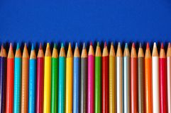 Row of pencil crayons. Row of colored pencil crayons on blue background Stock Photos