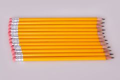 A row of pencils enter top left at an angle with erasers flush stock photography
