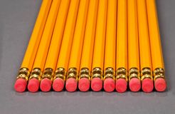 Row of pencils with erasers. Row of twelve yellow pencils with erasers on end, studio background royalty free stock image
