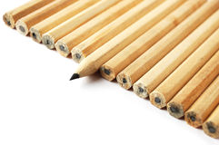 A row of pencils with one in different position Stock Photos