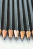 Row of pencils - vertical. Row of drawing pencils, with points toward viewer. Shafts of pencils lose focus toward the background. Shallow DOF royalty free stock photos