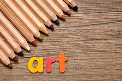 A row of pencils with the word art. On a wooden background stock image