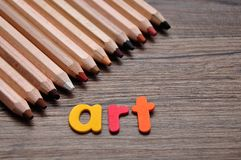 A row of pencils with the word art. On a wooden background royalty free stock image
