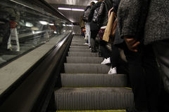 Row of people on mechanical stairs of the Barcelona metro. Royalty Free Stock Image