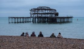 Row of people sitting on pebbly beach in Brighton UK on a wintry afternoon in December, in front of the ruins of West Pier. royalty free stock photography
