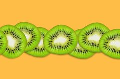 Row of pieces of sliced tasty beautiful ripe fresh kiwi fruit on orange table in kitchen. Top view. Cooking concept. Copy space for your text royalty free stock images
