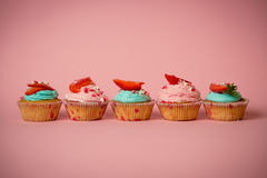 Row of pink and blue cupcakes with fresh strawberry on pink back Stock Photography