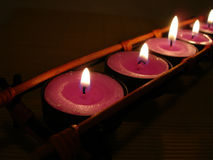 Row of pink candles in darkness Royalty Free Stock Photography