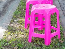 Row of pink plastic chairs. In the park Stock Photo
