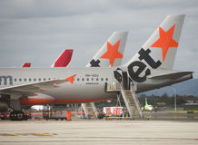 Row of planes at Adelaide Airport. Adelaide, Australia - June 25, 2016: Jetstar and Qantas planes prepare for boarding and departure at Adelaide Airport Stock Image