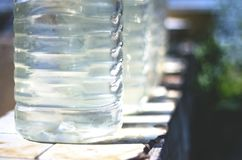 Row of Plastic Bottles Filled with Clean Water From a Public Well on a Bright Sunny Day. Water Supply Shortage, Climate Change. Concept stock photo