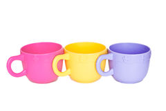 Row-plastic-cups. Row of three toy plastic cups on white background Stock Photos