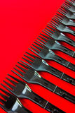 Row of plastic forks. Row of black disposable plastic forks on red background with copy space Stock Image
