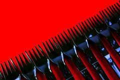 Plastic Forks. A line of disposable black plastic forks on a red background Stock Photography