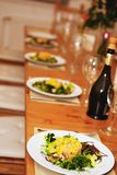 Row of plates with salad served on table Stock Photo