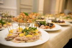 Row of plates with various cold appetizers standing on a table with a white tablecloth royalty free stock photo