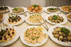 Row of plates with various cold appetizers standing on a table with a white tablecloth stock photo