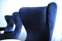 A row of plush chairs against sheer white curtains. Stylish, retro blue chairs in a bright lounge area royalty free stock photos