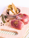 Row pork tenderloin with herbs on cutting board. Stock Images