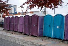 A row of portable rent toilets. Portable blue and lilac public toilets standing in a row royalty free stock photos