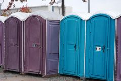 A row of portable rent toilets. Portable blue and lilac public toilets standing in a row royalty free stock image
