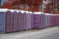 A row of portable rent toilets. Portable lilac rent public toilets standing in a row stock images