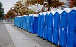 A row of portable rent toilets. Portable blue rent public toilets standing in a row royalty free stock images