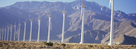 Row of power generating windmills in front of mountain range Stock Photo