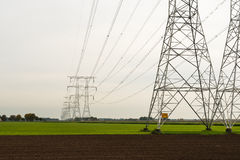 Row of power pylons in an agricultural area Stock Image