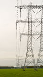 Row of power pylons in an agricultural area Royalty Free Stock Images