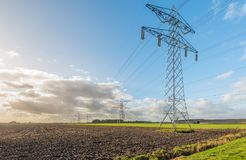 Row of power pylons at the edge of a plowed field Stock Images