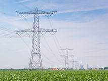 Row of power pylons and lines in a rural landscape Stock Photos