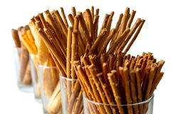 Row of pretzels, grissini and cheese sticks in glasses on white stock photo
