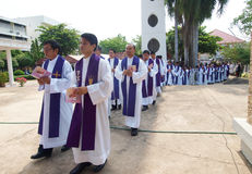Row of priests walking into church Stock Image