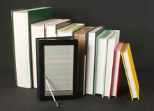 Row of printed books with electronic book reader stock photography