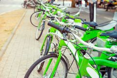 Row of public bicycle on rental station on city background. Eco-friendly and convenient transportation in the city. Close up, sele. Ctive focus. Space for text Royalty Free Stock Images