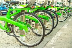 Row of public bicycle on rental station on city background. Eco-friendly and convenient transportation in the city. Close up, sele. Ctive focus. Space for text Royalty Free Stock Image