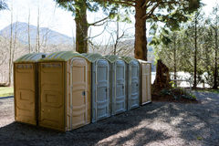 Row of public Portapotty toilets in a park Royalty Free Stock Images