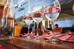 Row of pure drinking water glasses at summer terrace cafe. Royalty Free Stock Photo