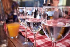 Row of pure drinking water glasses at summer terrace cafe. Stock Photo