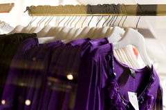Row of purple blouse garments on display. In a retail shop window Royalty Free Stock Image